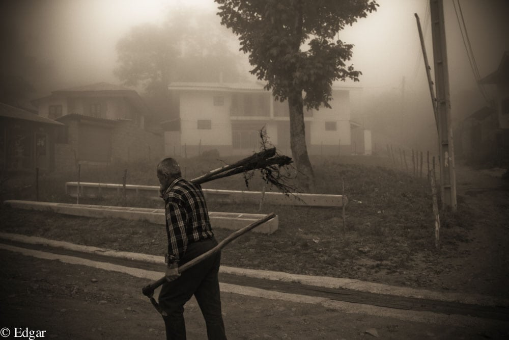 A men finishing his long day of hard labor and heading home in the fog.